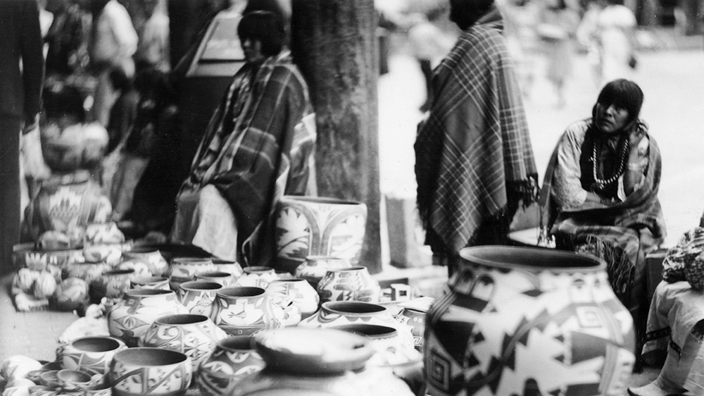 Women selling pottery on Palace of the Governors portal during Indian Market, 1938. Palace of the Governors Photo Archives No. 135047